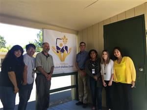 Staff in front of Integrated Wellness Center sign