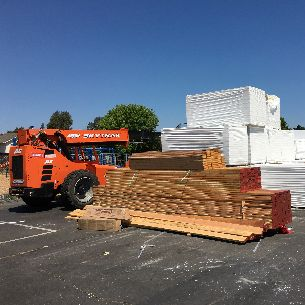 Lumber and construction vehicle at a school site