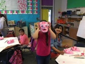 Migrant Ed student wearing paper mache mask