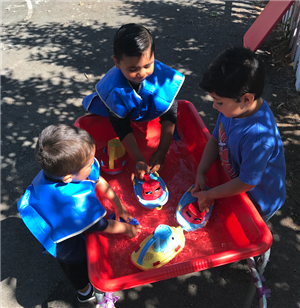 three boys at water table